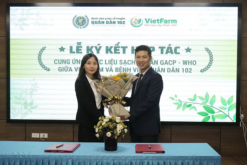 Đại diện Bệnh viện YHCT Xương khớp Quân Dân 102 tặng hoa cho đại diện Trung tâm Dược liệu Vietfarm